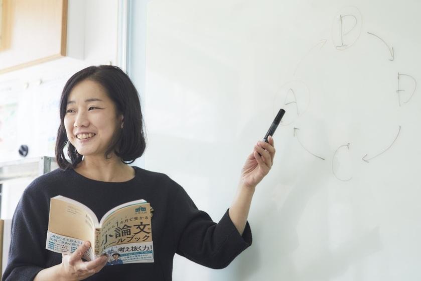 ホワイトボードの前で女性教師が授業をしている