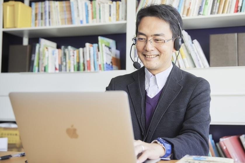 ヘッドホンをした男性がパソコンを操作している